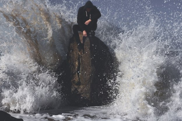Guy sitting on a rock with waves crashing in.
